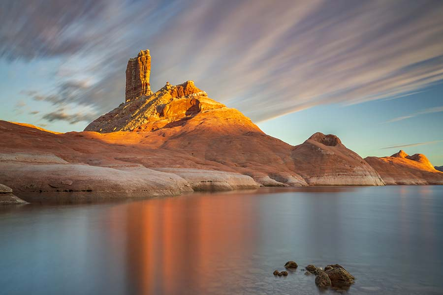 We have only one spot left for our Lake Powell Houseboat Workshop next September!  Learn more here: https://actionphototours.com/lake-powell-houseboat-photo-workshop/  On the evening this shot was taken, there was a slight breeze coming right towards us.  I decided to use a polarizer coupled with a 10-stop ND filter to achieve a 2-min exposure.  The long exposure created the smooth water and with the wind blowing right towards us, it helped to elongate the vibrant reflection.  Lake Powell is such an amazing place to photograph.  Hope you can join us next year!