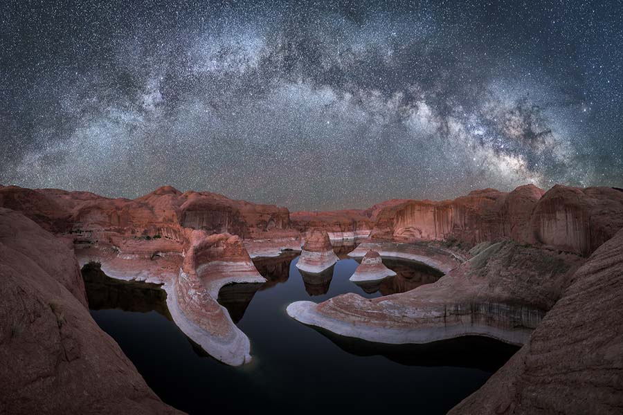 This image was captured during our workshop last week out at Reflection Canyon. It's a long hike out there and for some participants this was their first experience backpacking.  Definitely a great destination for your first time!  This panoramic was stitched together from around 6 vertical images. We started taking foreground shots in the blue hour and continued into the night hours. The water was very calm at Blue Hour but as we neared astronomical twilight, the wind started picking up. After it got completely dark the stars became blurry streaks as they reflected in the wind-blown water.  So I was glad we took the blue hour shots with the added bonus of the nice glow on the background cliffs! The sky was stacked from several different high ISO exposures for additional noise reduction.