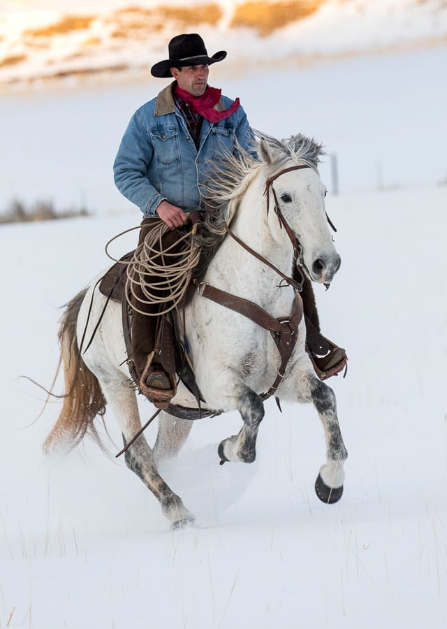 Cowboy riding in winters snow Horse Ranch Winter Photo Workshop