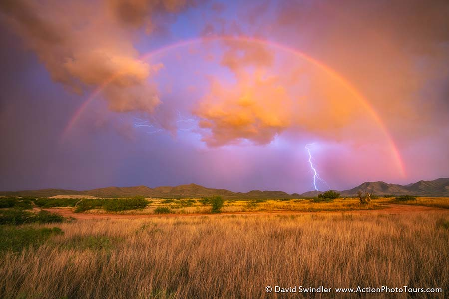 We have been having a blast on our Storm Chasing Workshops, especially with all the active monsoon activity over the past few days!  Here is a shot from our chase last night. As sunset approached, a large rainbow appeared.  But right as we started to photograph it, the rain began to fall in earnest.  We quickly drove further away to escape the rain and got there just in time to catch the last of the giant rainbow.  The wind was blowing and raindrops were quickly collecting on my lens.  I hooked up my lightning trigger and this shot was captured right in-between when I was blowing off my lens!  About 2 mins later, we were all running for cover as the rain started to pour down.  Dramatic lightning shows continued all around us for several more hours. What a fun night we had!!